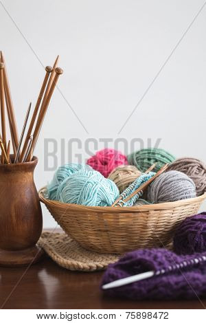 Knitting needles and yarn balls in basket