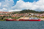 image of barge  - Red Barge with Stones and Sand near a River Coast - JPG