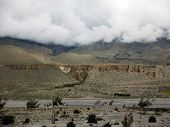 picture of mustang  - Caves used as housing next to a river in the dry Annapurna Himalayas of Mustang Nepal during monsoon - JPG
