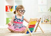 stock photo of indoor games  - child kid weared glasses playing with abacus toy indoor - JPG