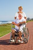 image of elderly couple  - a happy senior wife pushing her busband in wheelchair on beach vacation - JPG