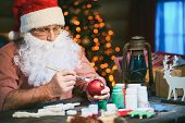 picture of ball cap  - Senior man in Santa cap and beard painting toy balls with gouache - JPG