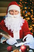 foto of letters to santa claus  - Portrait of happy Santa Claus answering Christmas letter - JPG