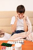 foto of home remedy  - Sick and Tired Teenager on the Sofa at the Home with Pills on foreground - JPG