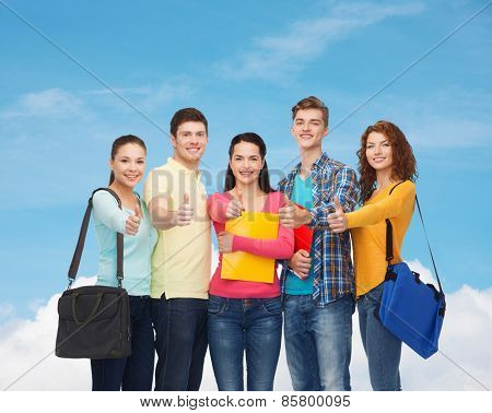 friendship, gesture, education and people concept - group of smiling teenagers with folders and school bags showing thumbs up over blue sky with white cloud background