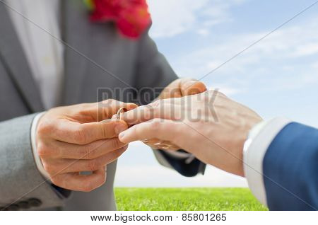 people, homosexuality, same-sex marriage and love concept - close up of happy male gay couple hands putting wedding ring on over blue sky and grass background