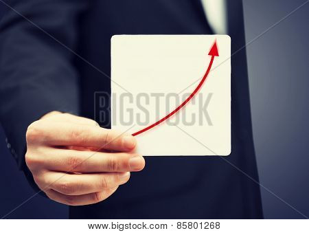 man in suit holding card with increasing graph on it