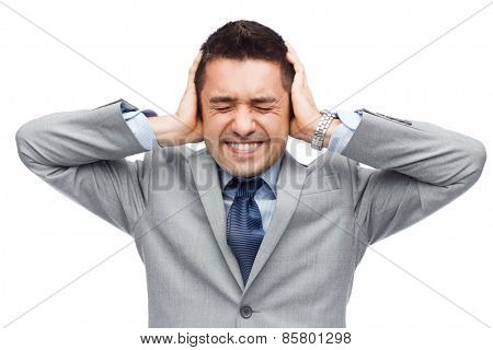 business, people, crisis and emotional pressure concept - businessman in suit covering his ears by hands