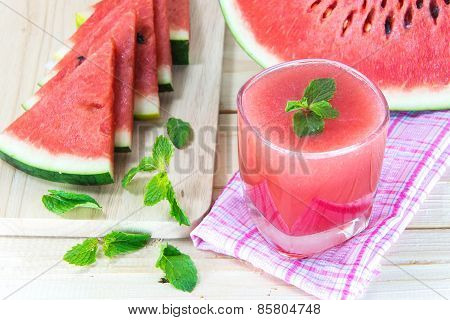 Glass Of Fresh Watermelon Juice With Mint Leaves And Sliced Fruit On Wooden Table. Selective Focus O