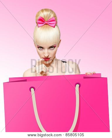 Glamorous girl with huge shopping bag on pink background