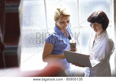 Two Businesswomen Having Informal Meeting In Office
