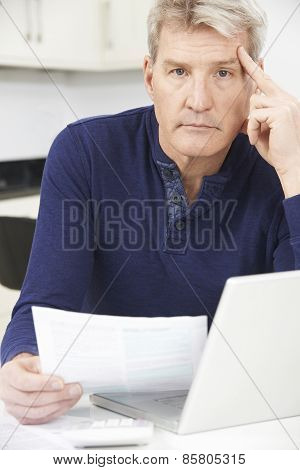 Worried Mature Man Looking Reviewing Finances At Home