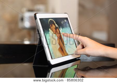 Hand Using A Tablet Watching Photos At Home
