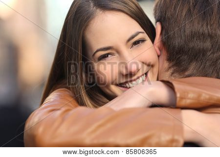 Happy Girlfriend Hugging Her Boyfriend And Looking At Camera