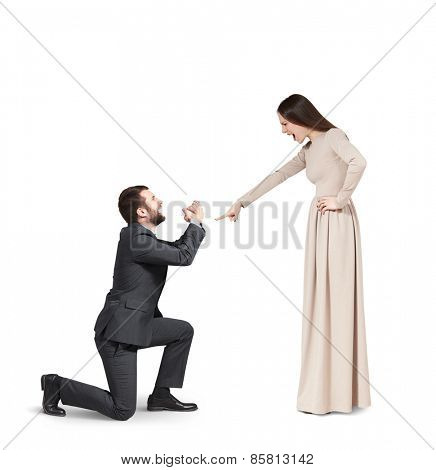 full length portrait of emotional couple over grey background. angry woman pointing and screaming at man, man standing on knee and apologizing. isolated on white background