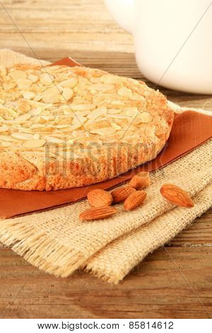 Dutch almond cake on a wooden table with slivered almonds on top. Also available in horizontal.