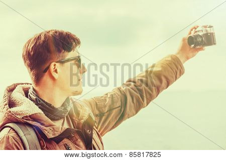 Man doing self-portrait with photo camera