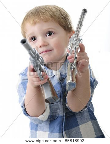 Close up of an adorable two year old playing cowboy with a gun in each hand.  Motion blur on  guns.  On a white background.