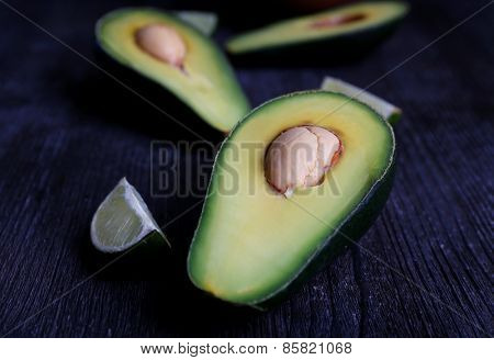 Sliced avocado with pieces of lime on wooden background