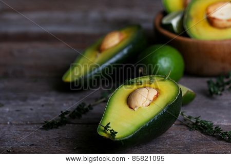 Sliced avocado with herb in bowl on wooden background