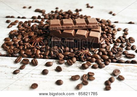 Chocolate with star anise and coffee beans on wooden background