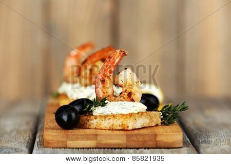 Appetizer canape with shrimp and olives on wooden background