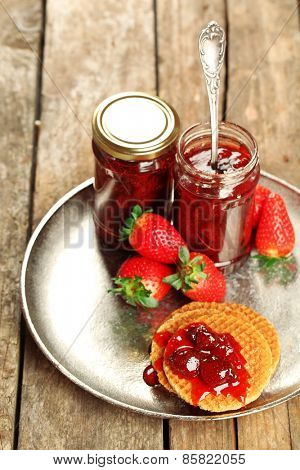 Jars of strawberry jam with berries and wafers on tray on table close up