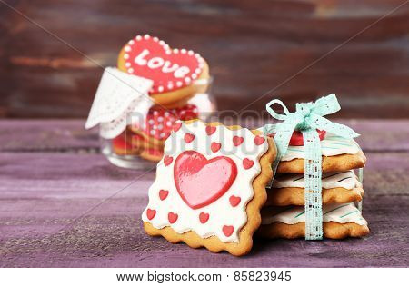 Heart shaped cookies for valentines day in glass jar on color wooden background