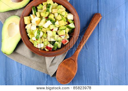 Salad with apple and avocado in bowl with napkin on wooden background