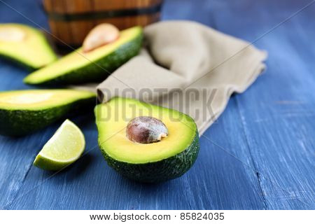 Avocado with lime on napkin on wooden background