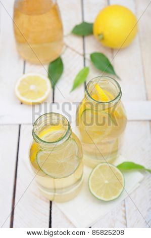 Lemonade In The Jug And Glasses With Lemons And Lime On White Rustic Table