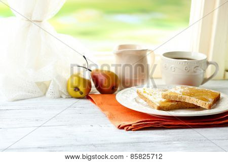 Toasts with honey on plate with cup of tea on bright background
