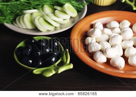 Mozzarella cheese with olives and greens on wooden background