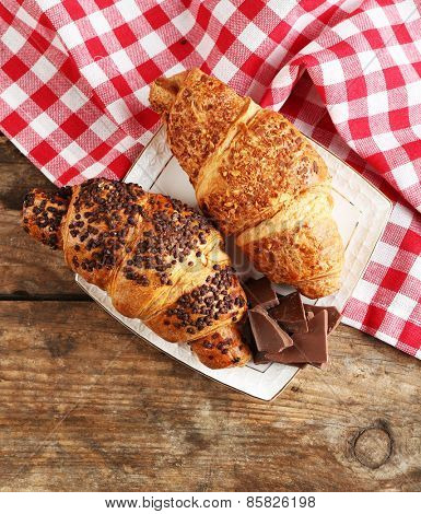 Fresh and tasty croissants with chocolate on plate, on wooden background