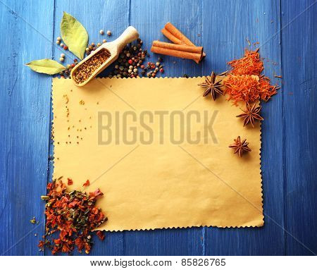 Different kinds of spices on blank paper sheet on wooden background