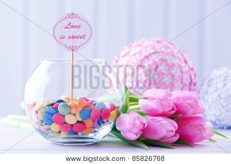Beautiful pink tulips with sweets in vase on table on wooden background