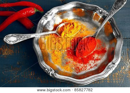 Carry and paprika with chili pepper on silver tray and color rustic wooden table background