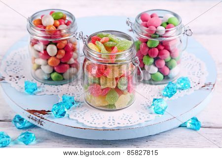 Multicolor candies in glass jars on color wooden background