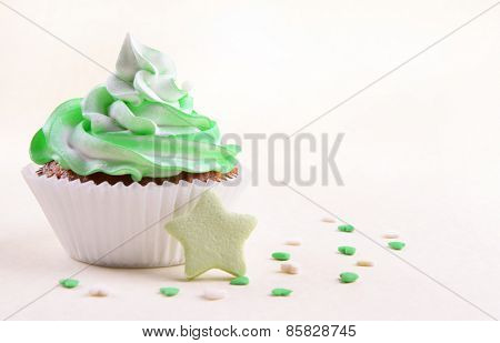 Delicious cupcake on beige background