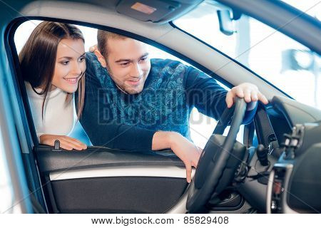 Interested couple examines a new car in showroom