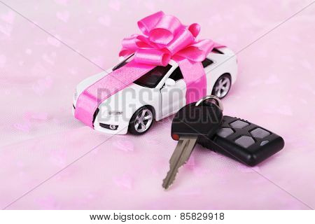 Keys and car with bow as present on pink background