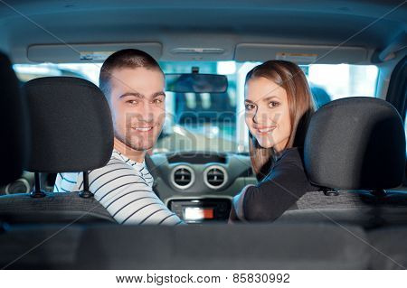 Couple inside the new vehicle in showroom