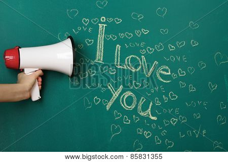 Hand holding megaphone on blackboard background