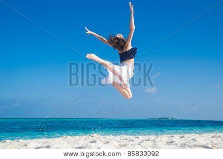 Young girl jumping at tropical beach, maldives
