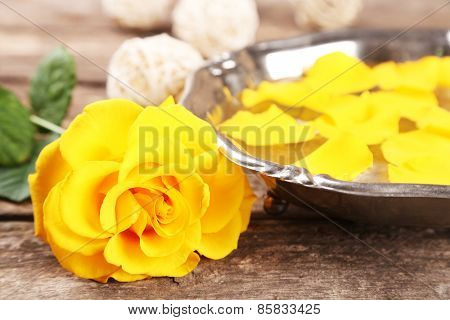 Rose flower and petals in bowl on wooden background