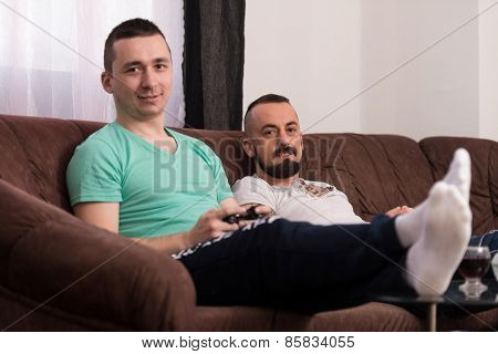 Smiling Male Friends Playing Video Games At Home