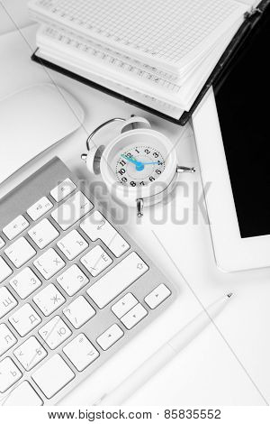 Office workplace with alarm clock close up