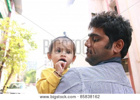 Indian Man holding kid and looking at her with love