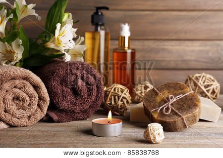 Beautiful spa composition with soap and candle on wooden background