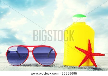 Bottle of suntan cream with sunglasses and sea star on table isolated on white